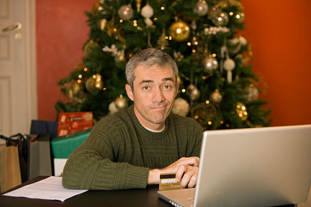 Man online shopping by Christmas tree